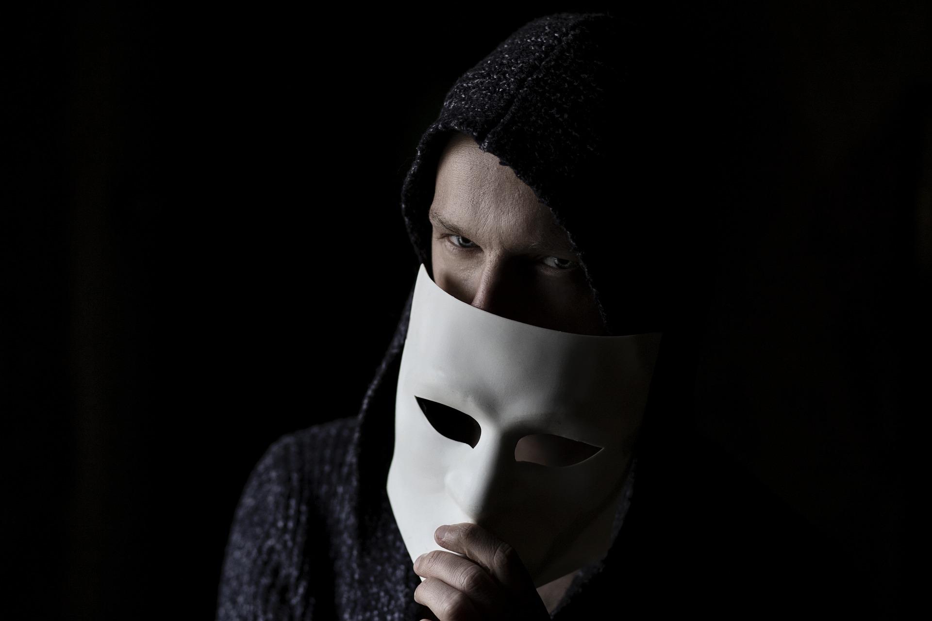 Mann, der sich unter einer Maske versteckt