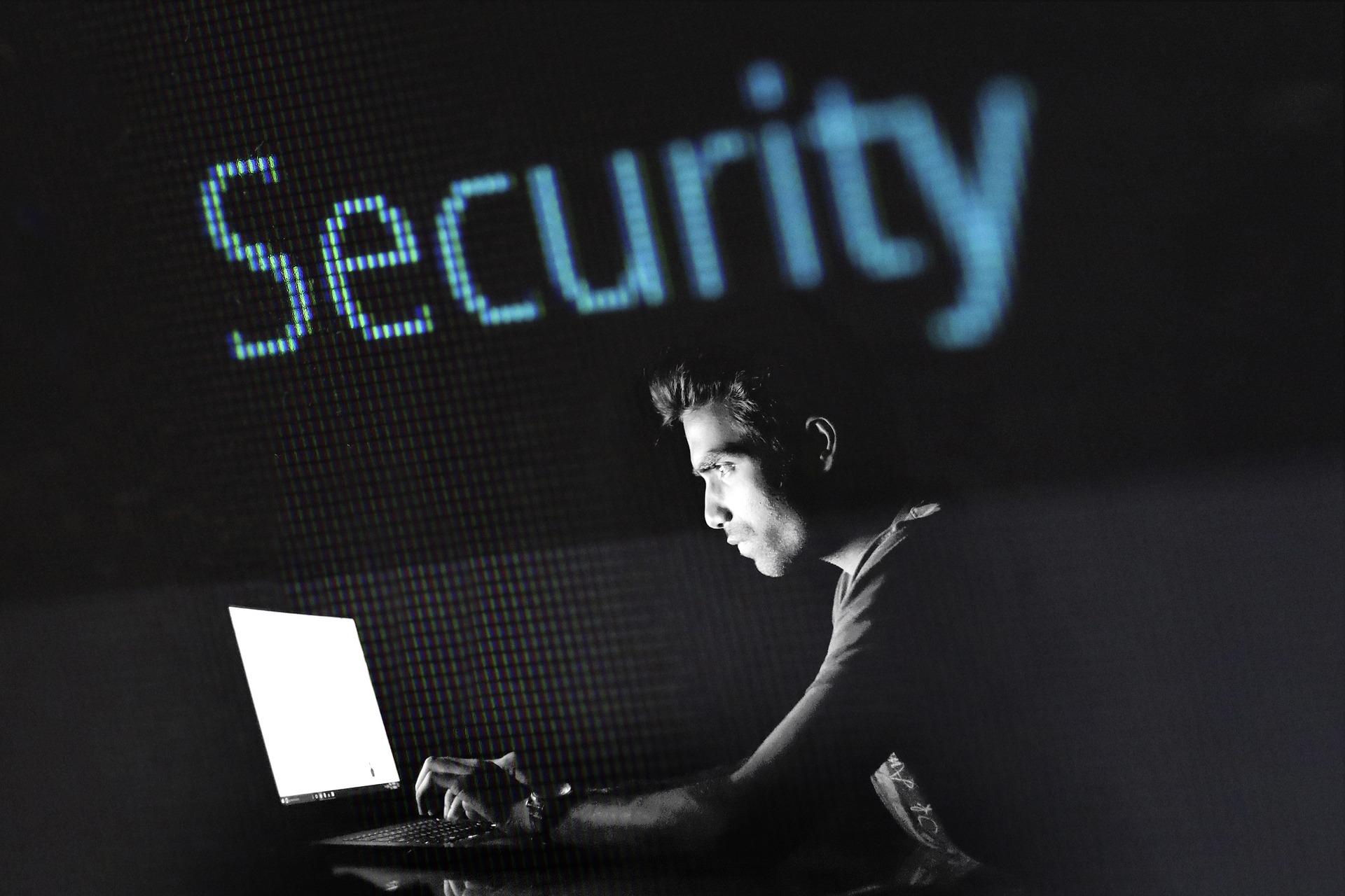 Mann arbeitet vor seinem Laptop mit der Überschrift IT-Sicherheit