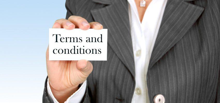 """frau im blazer hält karte mit aufschrift """"terms and conditions"""" in die kamera"""