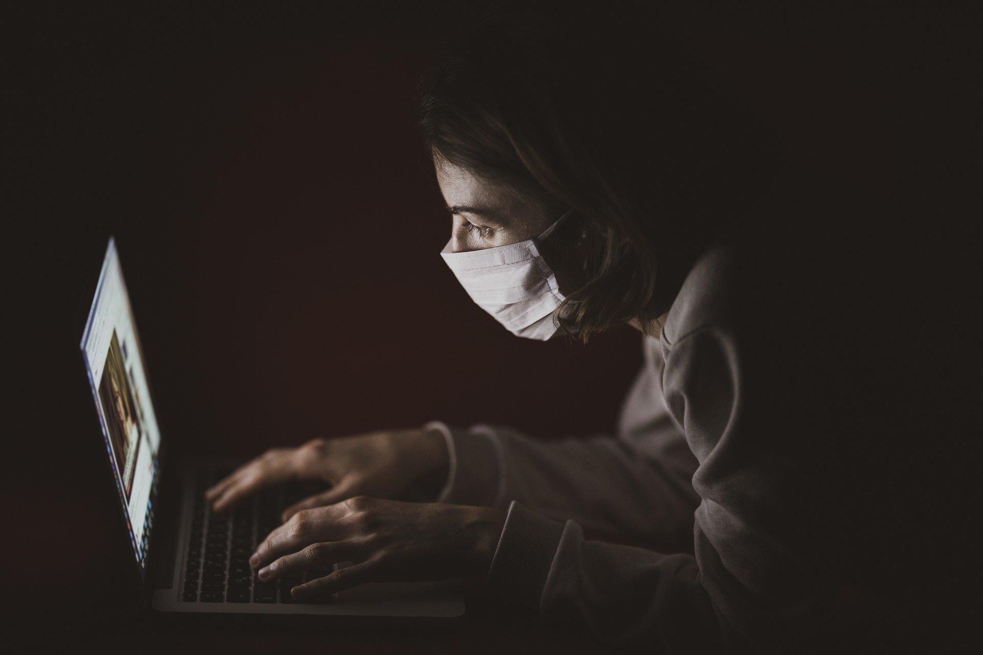 frau mit mund-nasen-schutz vor laptop